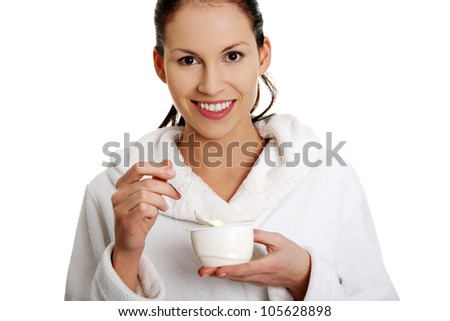 Young beautiful smiling woman wearing white bathrobe is eating yogurt. Isolated on the white background. - stock photo