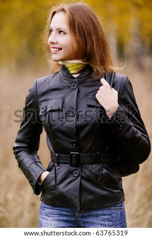 Young beautiful smiling woman with ladies' handbag looks in profile against autumn park. - stock photo