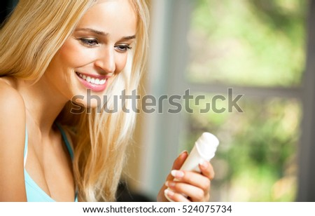 Young beautiful smiling woman with moisturizer, at home. Beauty and fashion theme concept.