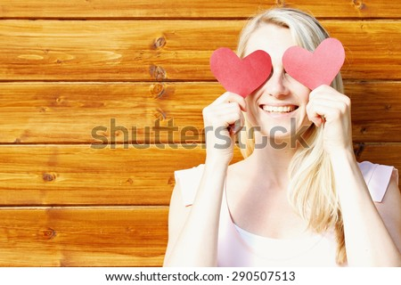 young beautiful smiling woman with paper hearts over eyes - fall in love concept