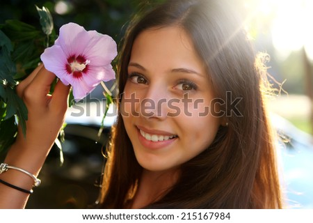 Young beautiful smiling woman with pink flower - stock photo