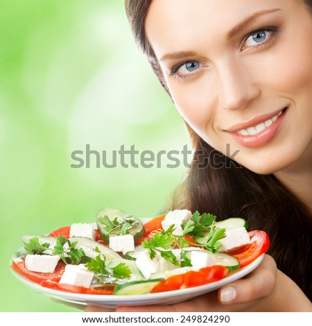 Young beautiful smiling woman with plate of salad, outdoor - stock photo
