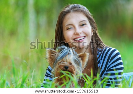 Young beautiful smiling woman with Yorkshire Terrier, against green of summer park. - stock photo
