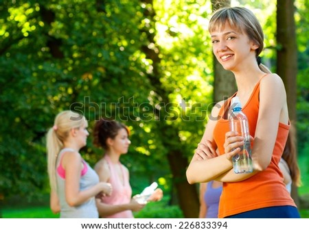 Young beautiful sport woman drinking water after exercising in nature. - stock photo