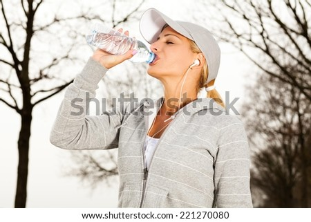 Young beautiful sport woman drinking water after running in nature. - stock photo