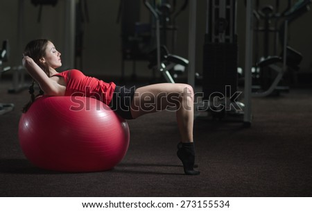 Young, beautiful, sports girl does exercises on a fitball at the gym - stock photo