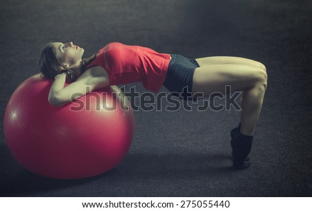 Young, beautiful, sports girl does exercises on a fitball at the gym. Toning - stock photo