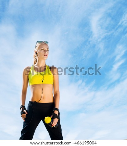 Young, beautiful, sporty and fit girl over sky background.