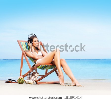 Young, beautiful, sporty and sexy woman relaxing on the beach - stock photo