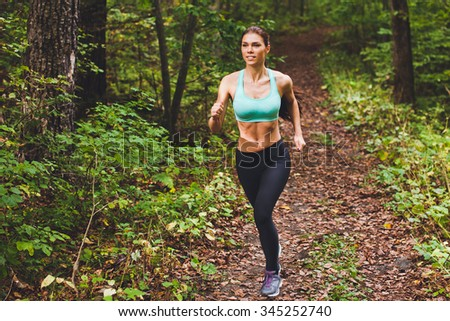 Young beautiful sporty girl in short green sports top training in green forest during summer autumn season with lots of fallen leaves on path. Front view with copy space full length portrait of runner - stock photo