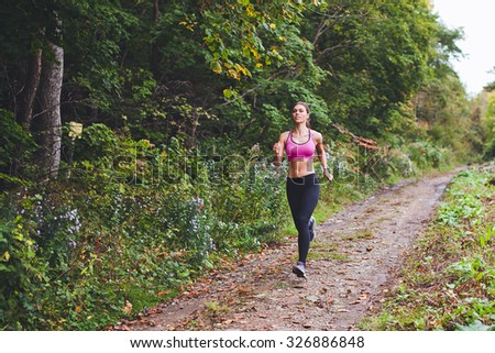 Young beautiful sporty girl training on country road near green forest during summer autumn season with lots of leaves fallen - stock photo