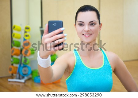 young beautiful sporty woman making selfie photo on smart phone in gym - stock photo