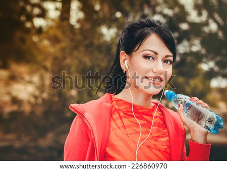 Young beautiful sporty woman with bottle of water - stock photo