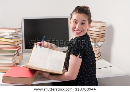 Young beautiful student girl holding her books - stock photo