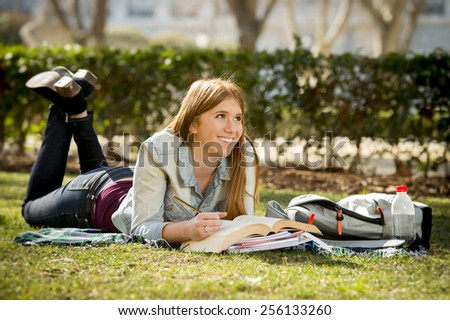young beautiful student girl lying on campus park grass with books on rug studying happy preparing exam in university and college education concept - stock photo