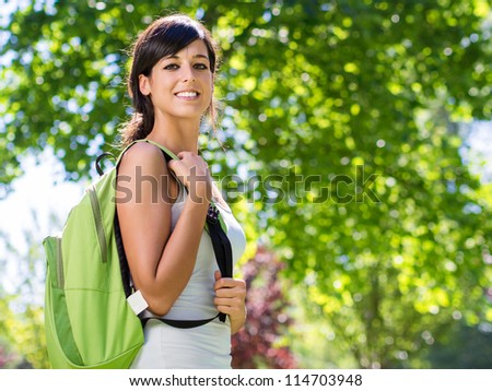 Young beautiful student looking at camera with backpack. Cheerful caucasian brunette. Green trees on background. - stock photo