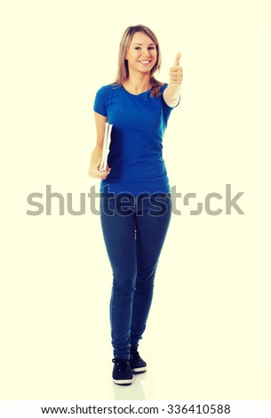 Young beautiful student woman showing OK, holding workbook. - stock photo