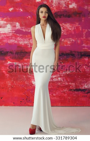 Young beautiful stunning woman posing in long elegant white evening dress and red shoes against stylish red background - stock photo