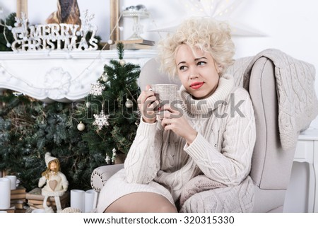 Young beautiful style woman relaxing on chair with cup of tea in front of Christmas tree decoration interior. Series of winter holiday photos. - stock photo
