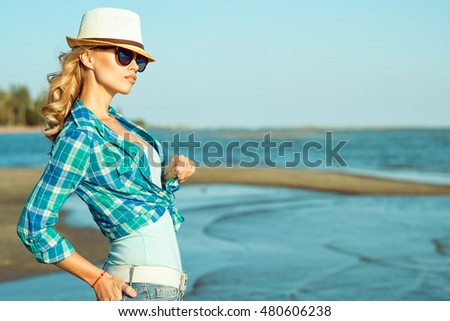 Young beautiful stylish blond lady in mirrored sunglasses and straw panama standing at the seaside and looking into the distance. Sea resort and summer fashion concept. Outdoor shot. Copy-space