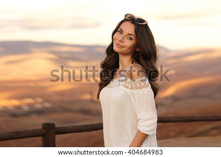 Young beautiful stylish calm girl standing against magnificent view on valley and hills at sunset. Pretty woman traveling