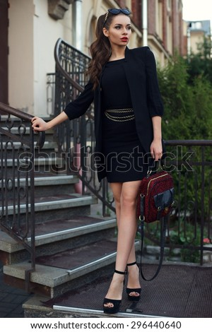 Young beautiful stylish classy girl wearing black dress and coat, holding red handbag, standing and posing at stairway.  - stock photo