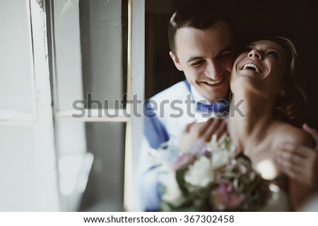 Young beautiful stylish couple embracing and kissing. Beautiful woman in a white wedding dress and handsome man in suit. - stock photo