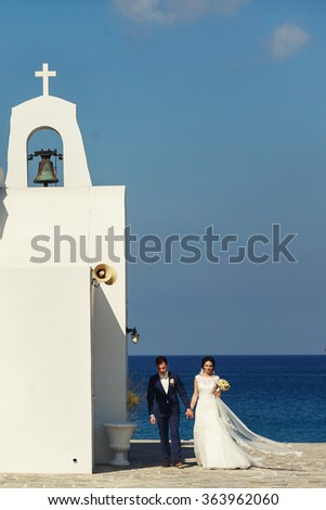 Young beautiful stylish couple newlyweds outside the church on the day of their wedding on the island of Santorini, Greece. - stock photo