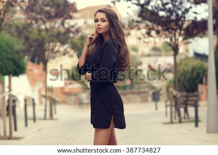 Young beautiful stylish girl in black summer dress walking and posing between trees at alley