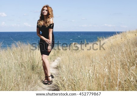 Young beautiful stylish girl posing on the beach. Stunning woman wearing black dress. Pretty model with long curly hair. Outdoors, lifestyle