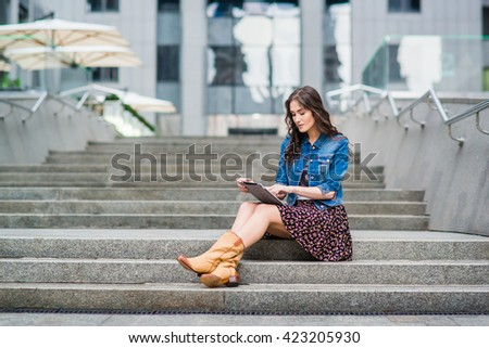 Young beautiful stylish girl sits on steps and holding hands in the tablet. Girl student communicates in social networks with friends. - stock photo