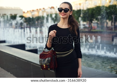 Young beautiful stylish girl walking and posing in short black dress in city near fountains. Outdoor summer portrait of young classy woman - stock photo