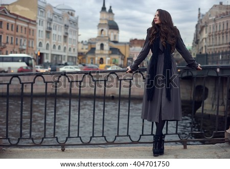 Young beautiful stylish girl with curly hair wearing black dress, scarf and gray coat standing near cast iron fence at city streets on a spring or autumn day