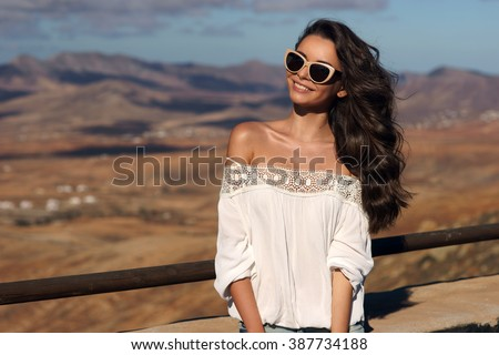 Young beautiful stylish happy smiling girl standing against magnificent view on valley and hills at sunset. Pretty woman traveling