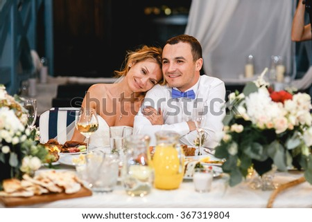 Young beautiful stylish smiling newlywed couple sitting at the wedding table with food and festive decor.