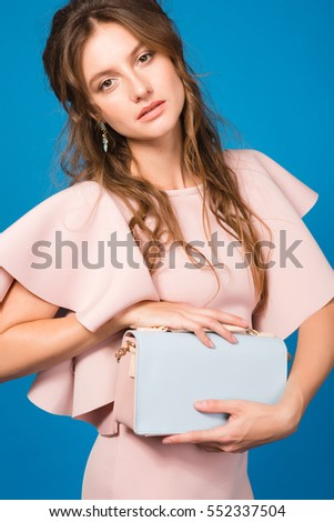 young beautiful stylish woman in luxury pink dress, holding purse, sexy, trendy style outfit, spring summer trend, bohemian hairstyle, natural look make-up, blue background