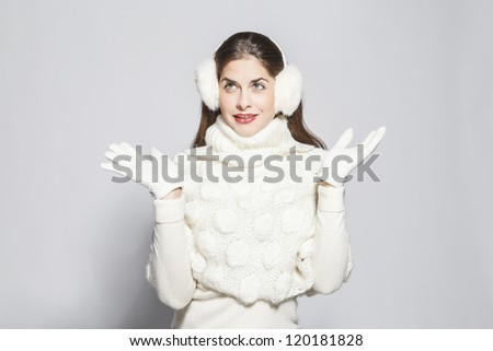 young beautiful surprise woman total white winter look. on grey background. - stock photo
