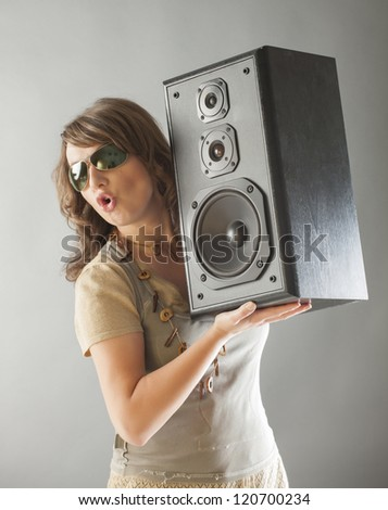 Young beautiful surprised woman with sunglasses holding big wooden speaker and listening music - stock photo