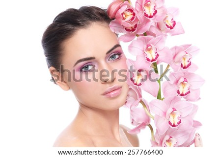 Young beautiful tanned healthy girl with clean pink make-up and orchid over white background - stock photo