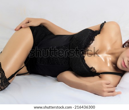 Young beautiful tanned Sexy woman wearing elegant lingerie lying on bed - stock photo