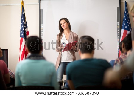 Young beautiful teacher gives lecture to students in classroom - stock photo