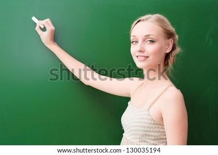 young beautiful teacher writes on the blackboard with chalk - stock photo