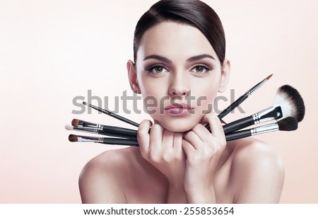Young beautiful teen girl with makeup brushes near her face, skin care concept / photoset of attractive brunette girl on beige background   - stock photo