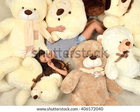 Young beautiful teenage girl lying with many teddy bears soft toys happy smiling and looking up at home warm color carpet - stock photo