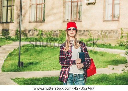 Young beautiful teenager girl student of the graduate applicant in red hat standing near the campus, university, school, education with a backpack choice, spring green park, mysterious look
