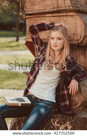 Young beautiful teenager girl student of the graduate applicant sitting near the sculpture of old books near the campus, university, school, education with a backpack choice, spring green park  - stock photo