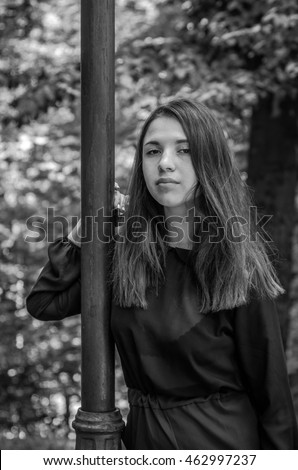 Young beautiful teenager girl with long hair walking in Striysky park in Lviv, posing near a lamp to illuminate the bushes and trees