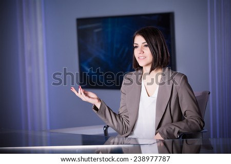 Young beautiful television announcer talking to audience at studio during live broadcasting.Transmission with serious smiling journalist woman.Television anchorwoman at studio during live broadcasting