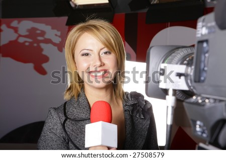 young beautiful television news reporter in front of the video camera smiling and looking at the camera in studio in live transmission