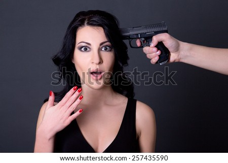 young beautiful terrified woman hostage and male hand with gun over grey background - stock photo